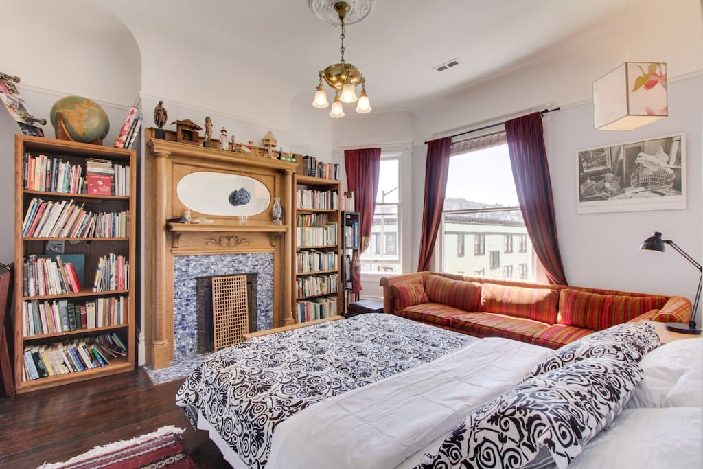 The room has high ceilings, a classic mantlepiece, and bookshelves.