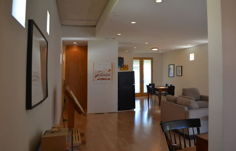 Entry foreground, living area to the right, kitchen to the right, bathroom ahead behind the sliding door.