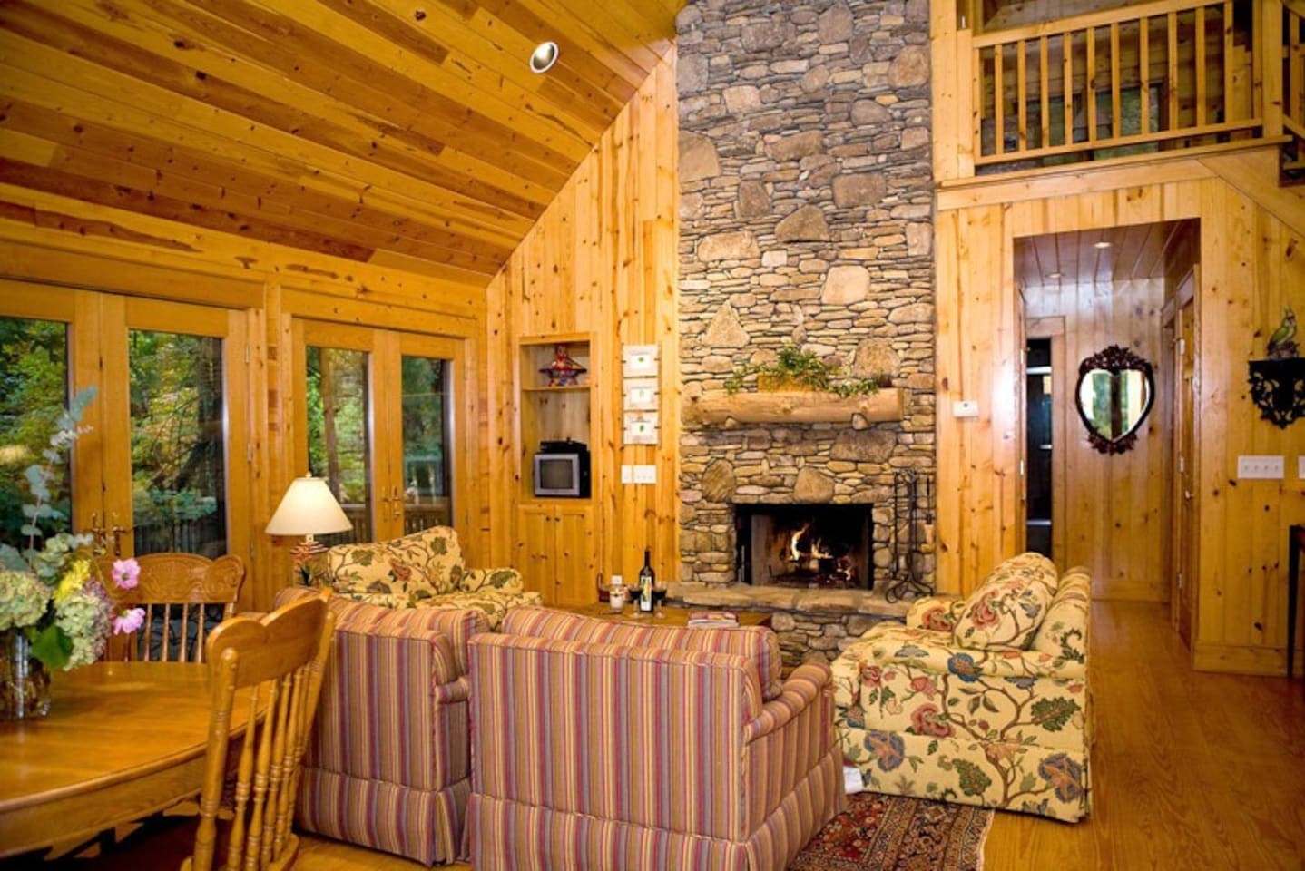 The living room is enhanced with a stone fireplace, vaulted ceiling and french doors.