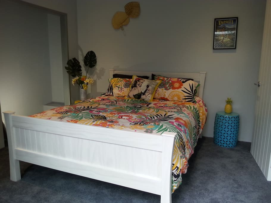 Queen bed facing a ranch slider with a small private courtyard.