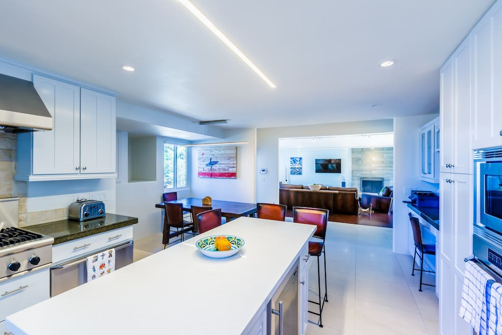 Fully stocked kitchen with state of the art appliances and ample room for seating and serving.