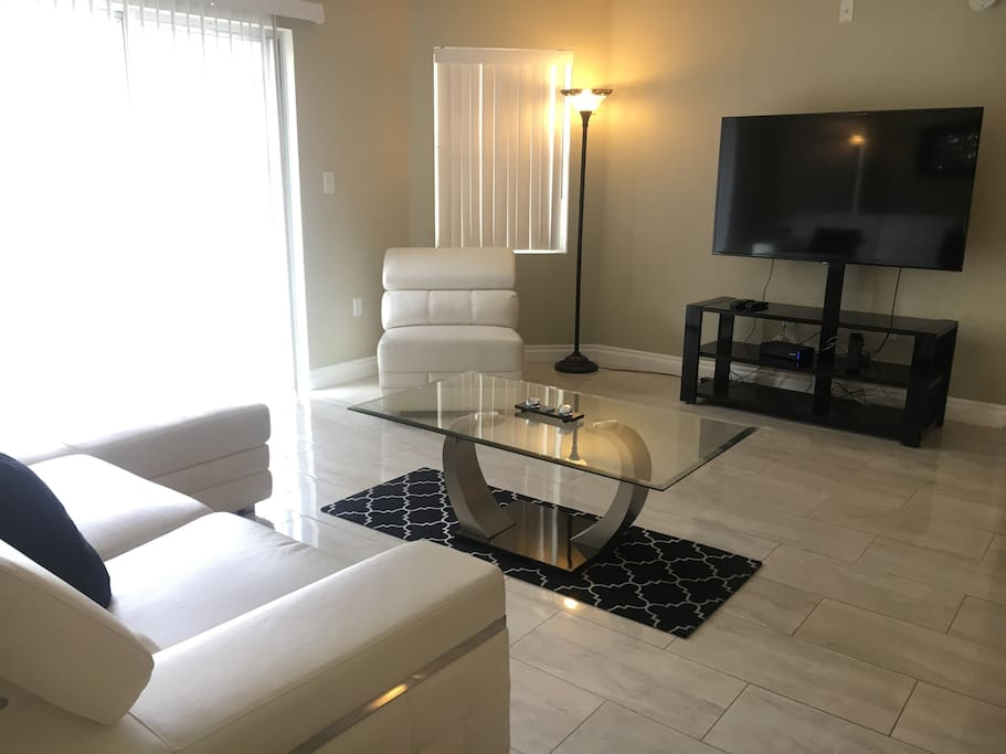 lovely white couches very comfortable and a glass living room table.