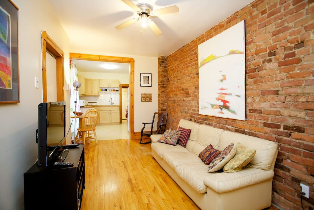 Living room with original art, flatscreen cable TV and view of newly renovated kitchen.