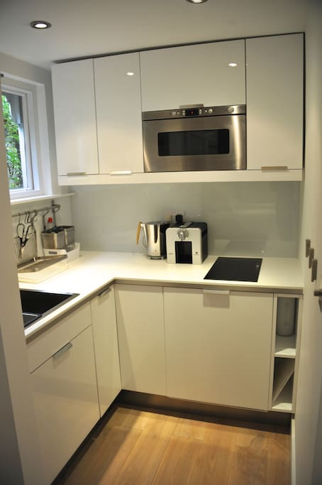 Kitchen with hob, refrigerator, microwave, tea kettle, Nespresso machine, and of course dishes and cutlery.