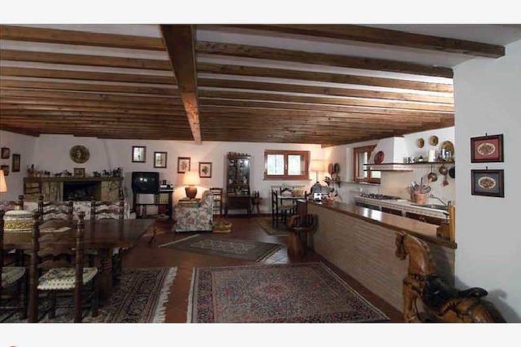 Grande salone con cucina in muratura e legno attrezzata di tutto. Due tavoli dove possono mangiare trenta persone sedute.