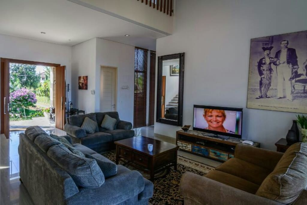 Main living room. Includes a large LED TV, a coffee table, cozy sofas, and complimentary Wi-Fi.