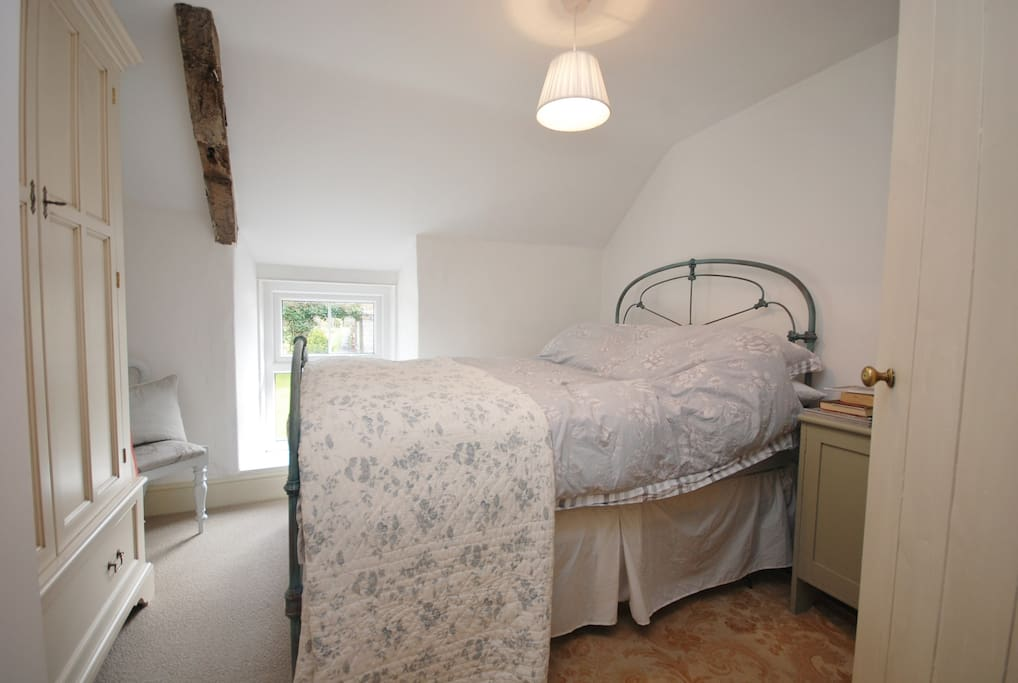 Double bedroom complete with original beam. An original antique iron bed. Large wardrobe and dressing table area. Views over the garden.