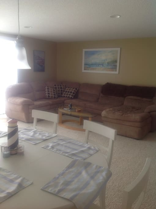 Large family room with big screen TV and walk out deck with beautiful view