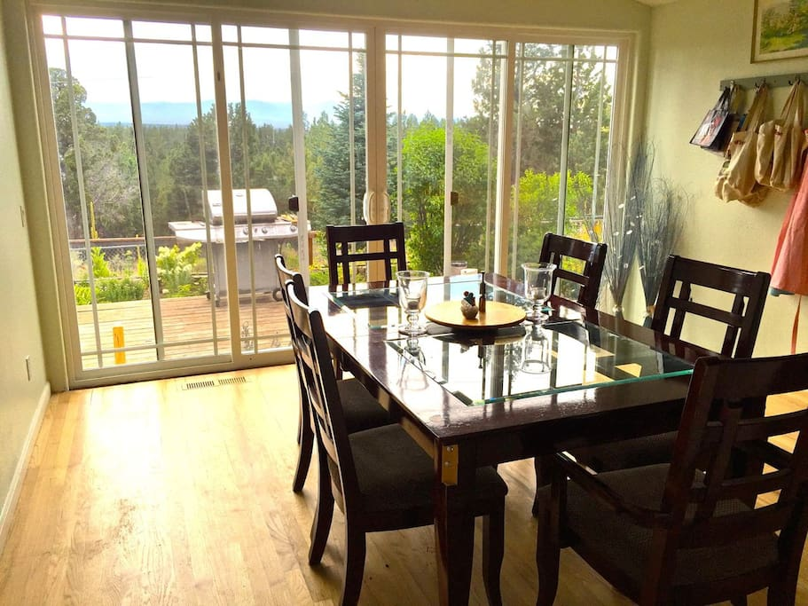 Bright and airy dining area with patio doors that open onto the deck and mountain views beyond.