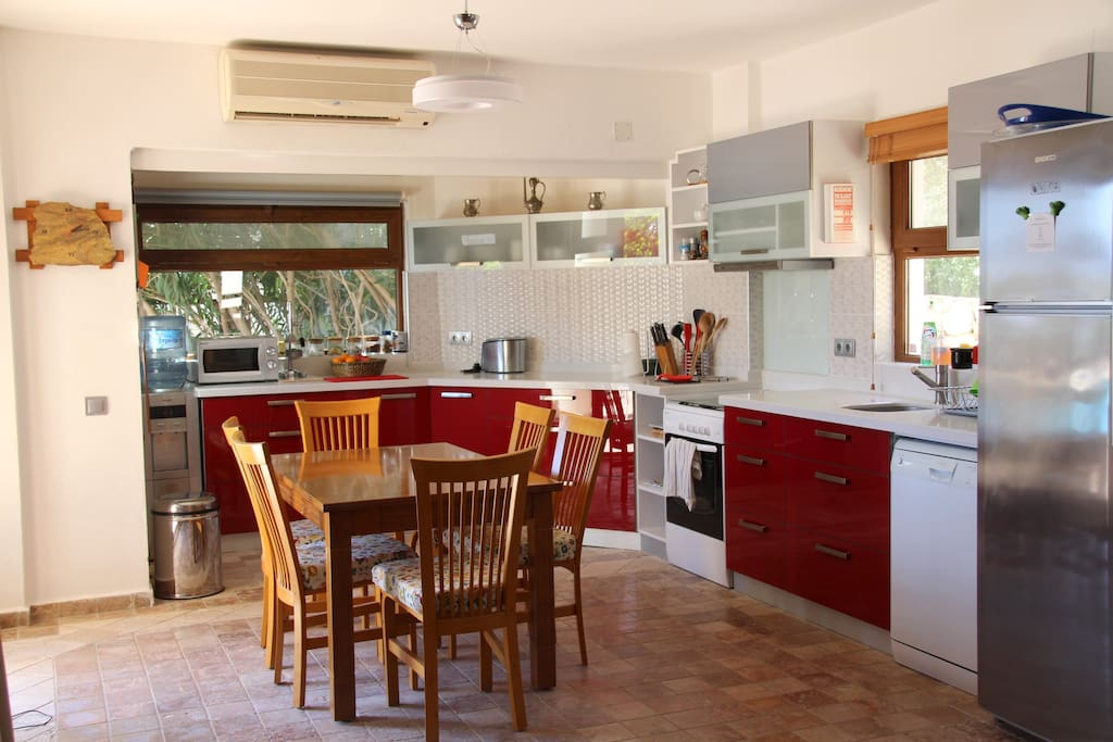 Modern kitchen with dining area, cooker, dishwasher, microwave and fridge/freezer.
