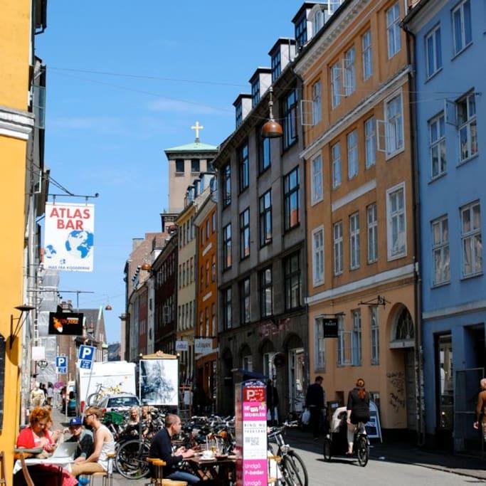 Studiestræde with many coffee shops, restaurants and shops. Bakeries, more coffee shops and and  a kiosk store just around the corner.