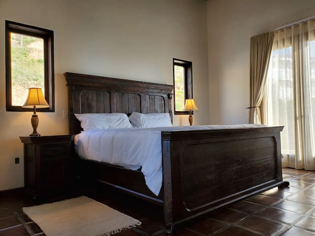 King Size Ocean View Bedroom #2 with private bathroom, fireplace and high vaulted exposed beam ceilings.