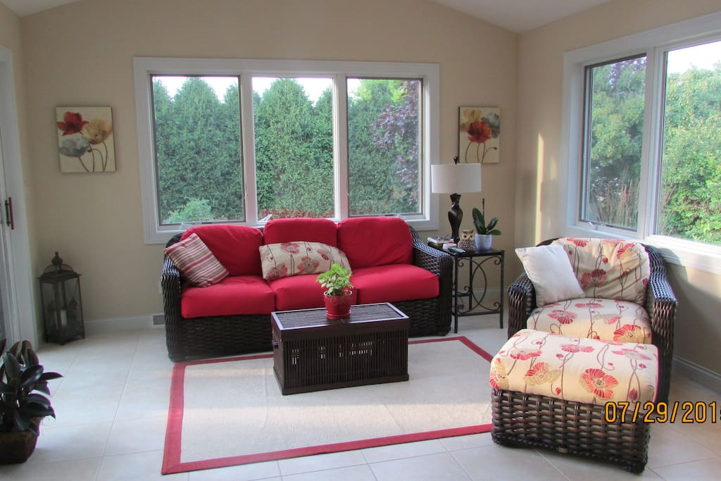 Sun room with TV and backyard/deck access.