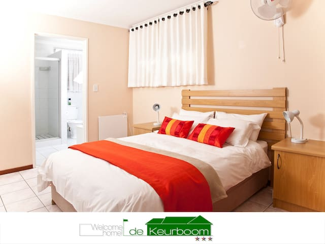 Master bedroom with En-Suite. A double bed with crisp white linen. Plenty of cupboard space. The room has a wall heater and during winter months we supply an electric blanket. There is a roof fan for warm summer nights. We also supply a hairdryer.