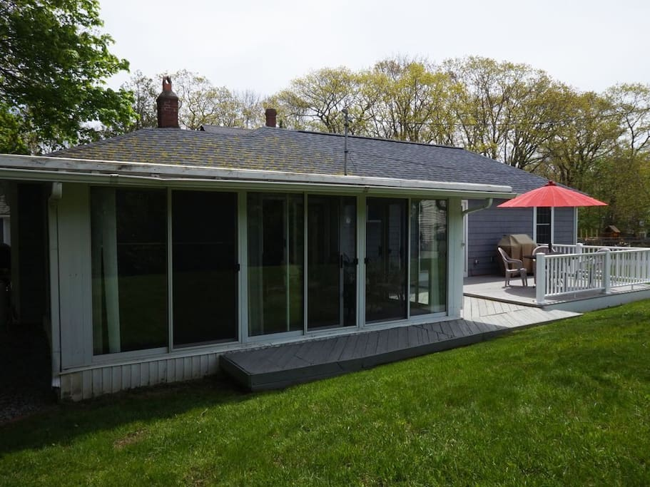 The sliding doors surrounding the three-season porch can be closed, screened, or opened fully