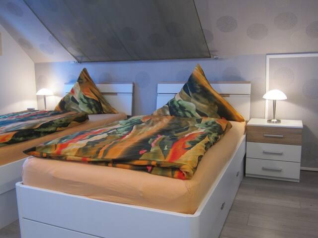 Schlafzimmer mit 2 Betten, die man auch zusammenstellen kann
