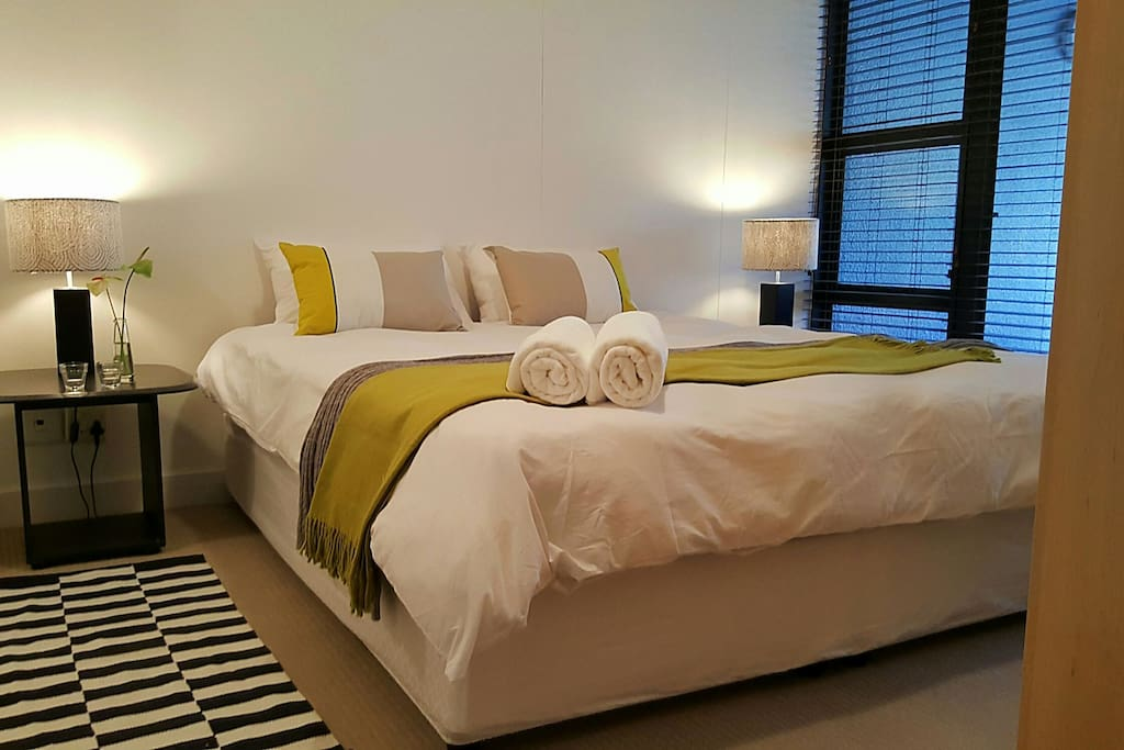 Bedroom with king extra length bed, leads onto open balcony. Ensuite bathroom.
