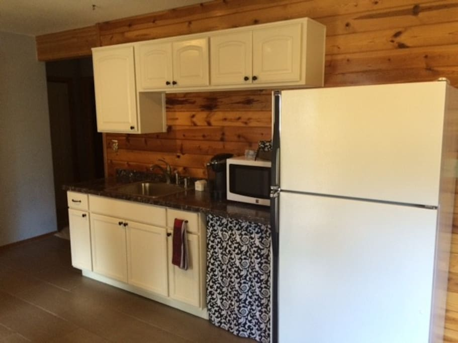Kitchenette with microwave, coffee maker, fridge and sink.