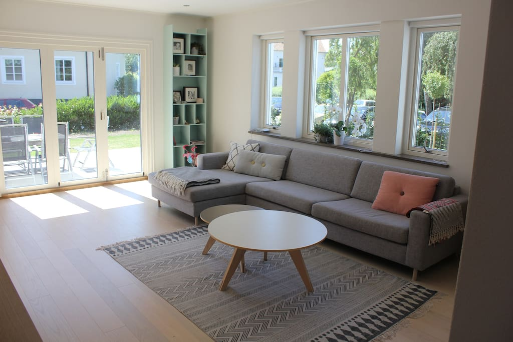 Romslig stue/hverdagsrom, innredet med skandinaviske møbler. Utgang til terrasse og hage.