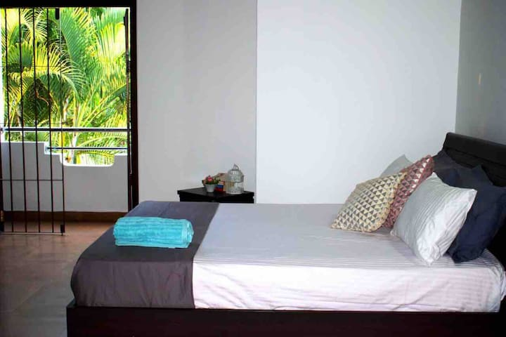 Bedroom with a private balcony view with air conditioners