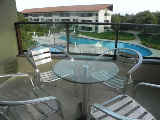 Varanda decorada com mesa e 04 cadeiras. Uma ótima vista para a piscina.