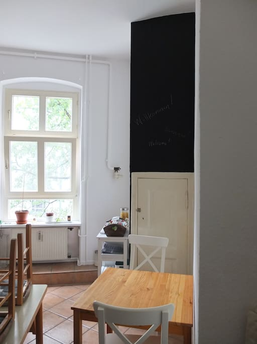 Sunny kitchen and high brigth white walls and a chalkboard accent wall.  View to the big tree in the courtyard and sky,