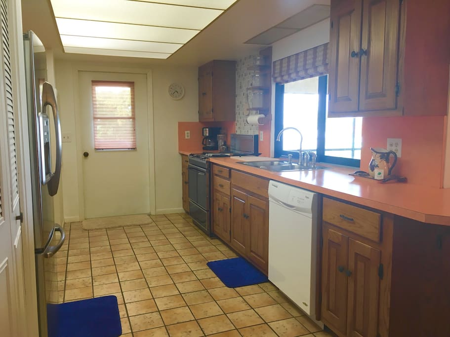 Kitchen has stainless steel fridge with ice maker , dishwasher , stove , oven pots pans dishes blender coffee maker . Home away from home