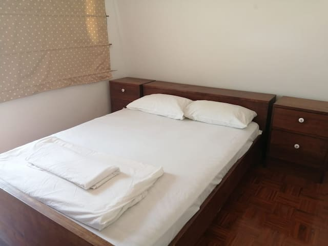 Second bedroom with queen bed, mosquito net over bed and AC Unit.