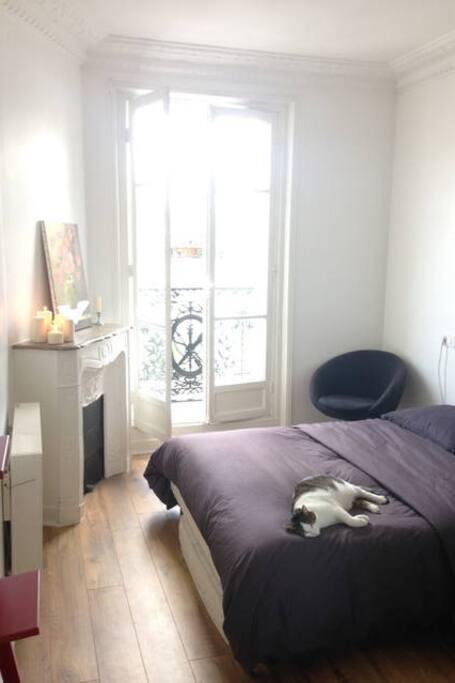 Chambre à coucher avec lit double. volets et portant vêtements.