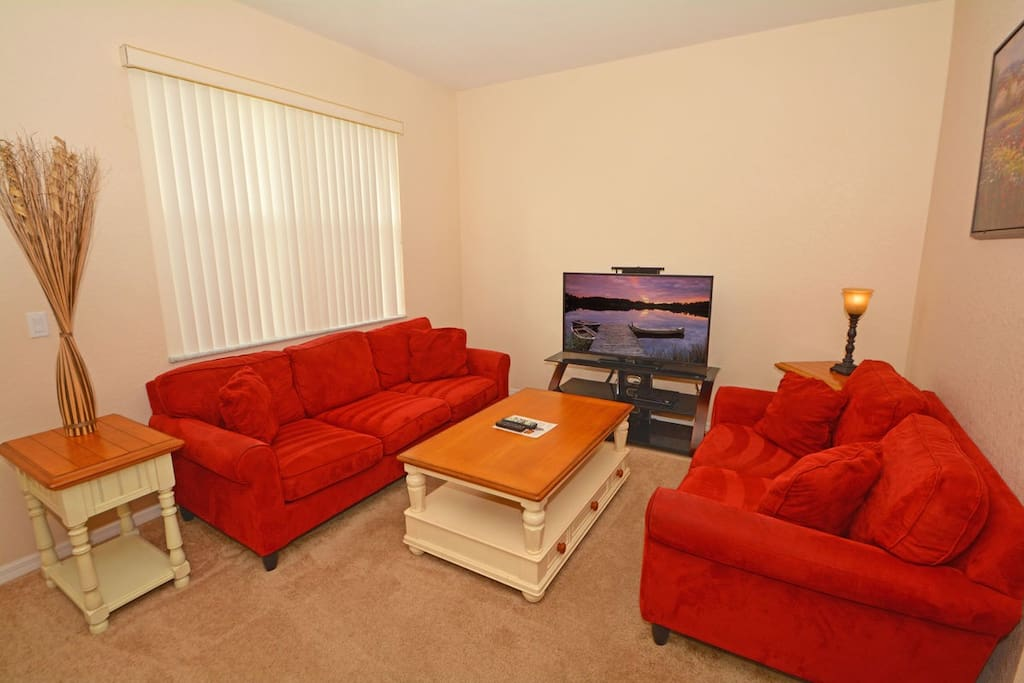 Main living area which has plush sofas, large flatscreen TV and sliding doors to small patio area