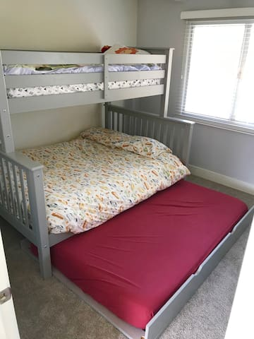 Kids bedroom has bunk bed with pullout trundle.  Top bunk is single (also known as twin) size mattress, bottom bunk is full size mattress, and trundle with a memory foam mattress.  The closet is full of toys and a lego bin.