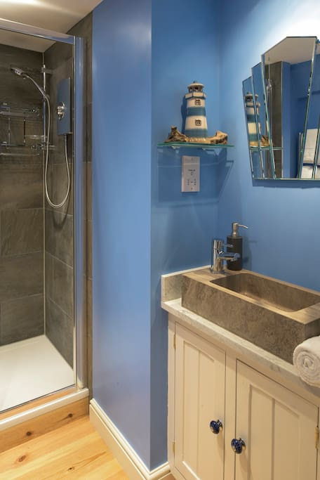 Mr Jones en-suite with powerful shower, stone wash basin on marble top counter, and Art Deco mirror.