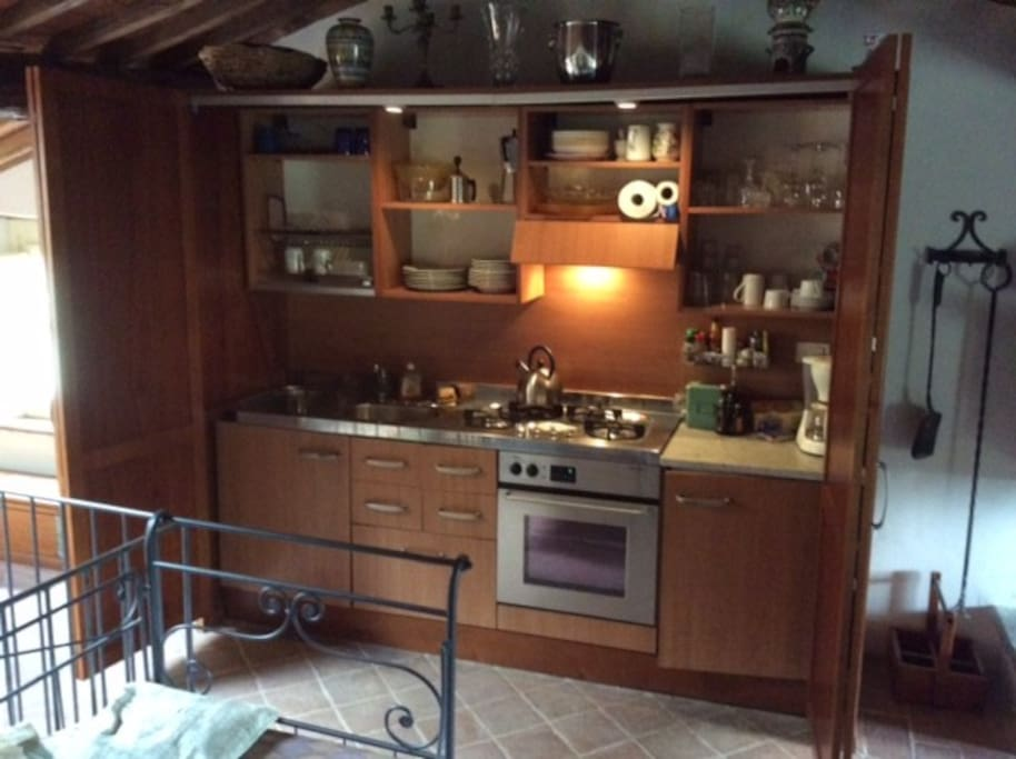 Kitchen with stove, oven, fridge and sink and all utensils, toaster, coffee maker.
