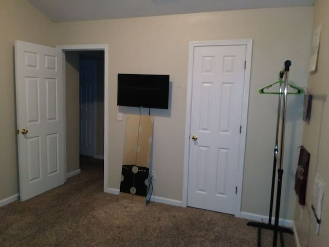 Clothing rack with hangers. 32 inch flat screen tv mounted on the wall, with guest Netflix account.