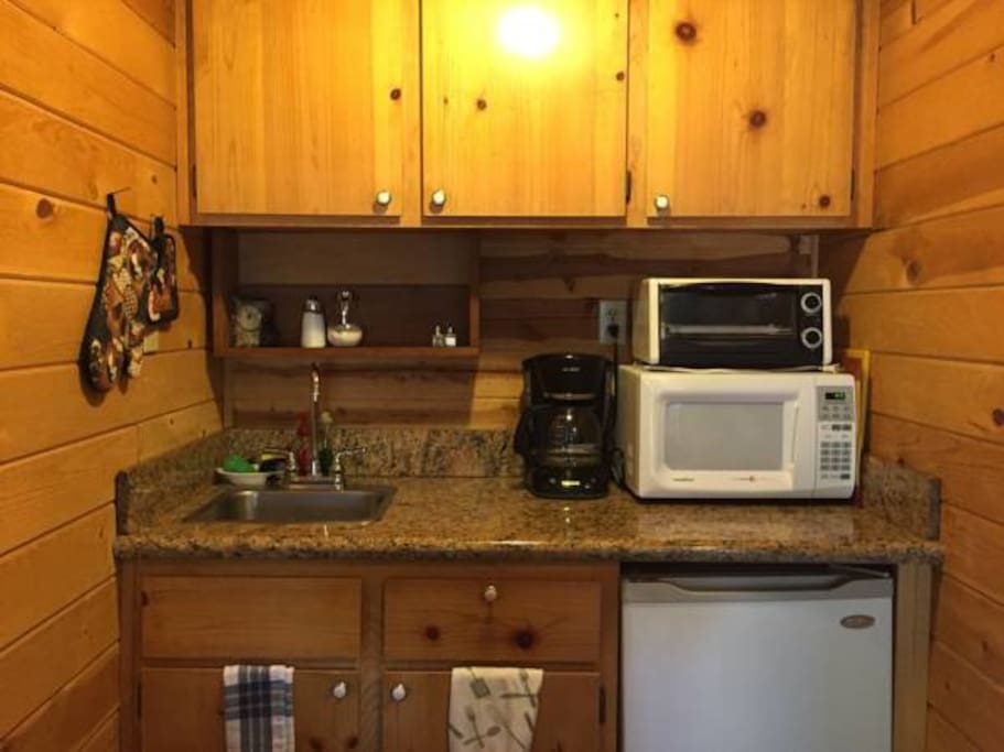 Mini kitchen view. Complete with utensils, microwave, toaster oven, coffee maker, and mini fridge. If you need to cook a complete meal, you're free to use the community room that offers a full kitchen or use any of the gas grills on site.