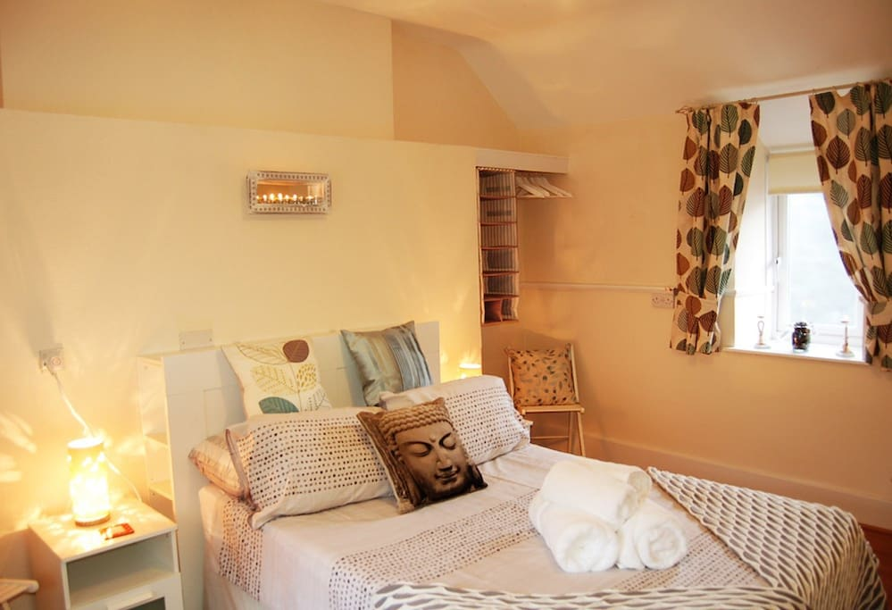 Master bedroom with comfortable double bed and TV