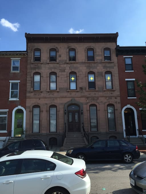 Full view of apartment building from street level. Windows with stars indicate the space for rent.