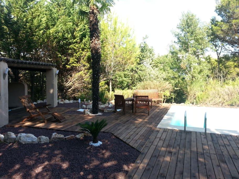 Grande terrasse aménagée au bord de la piscine : chaises longues, petit salon, hamac