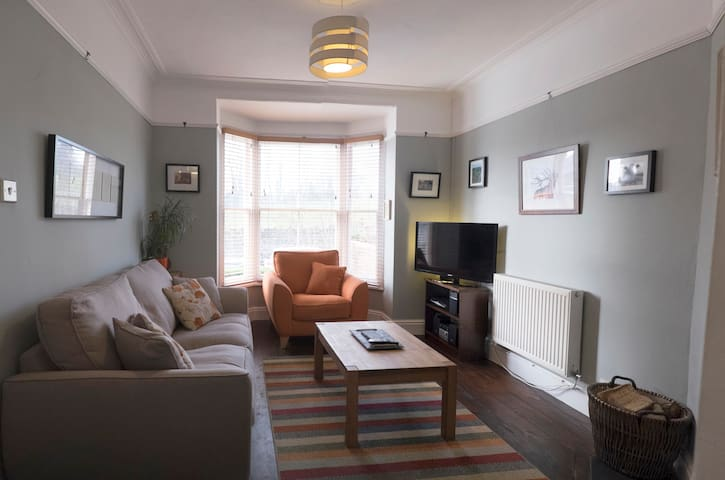 Living room with comfy sofa and chair, TV, wood burner and views across the park.
