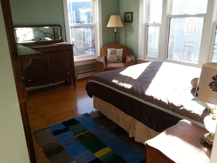 Queen sized bed, dresser, large windows view of the water.