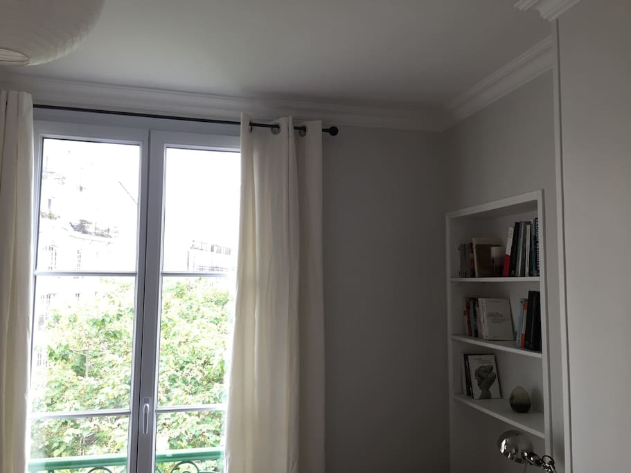 Living room window, wide open on a parisian place with trees. Not overlooked
