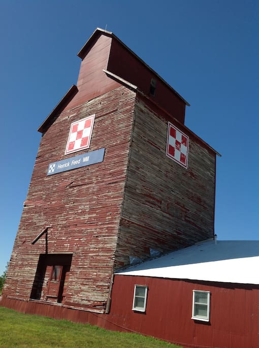 Nostalgic, weathered grain elevator stands tall next to the tin shed that houses your rooms.