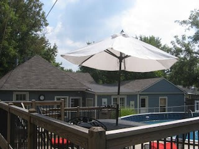 pool, attached deck with two tables/seating/umbrellas, back of house