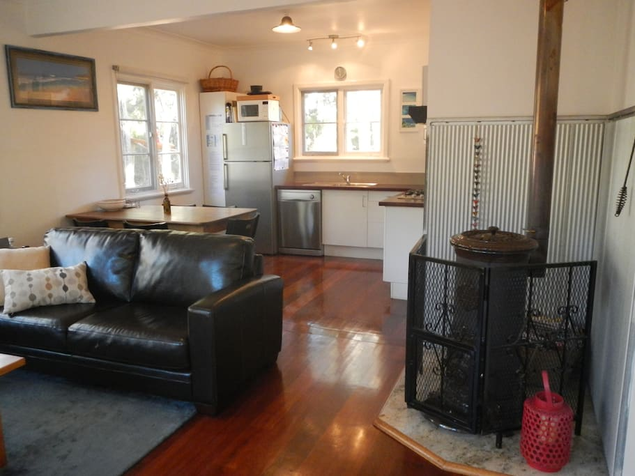 Open plan living,  dining and kitchen with wood pot belly heater