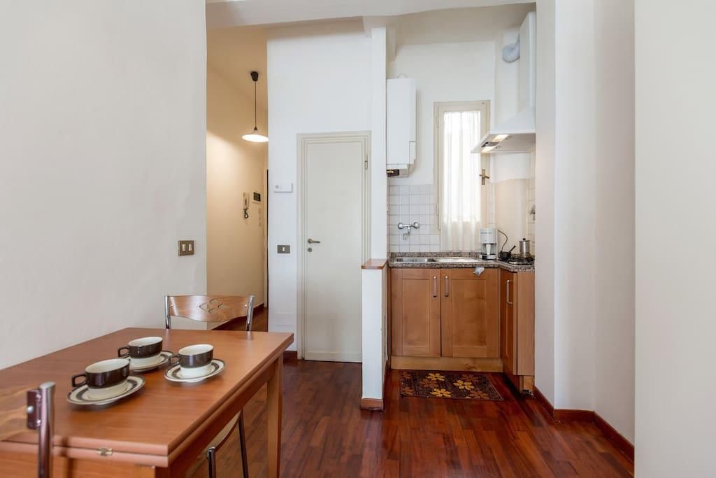 Angolo cottura completo con  cucina con due fuochi, cappa aspirante, frigorifero, lavello, stoviglie (nuove) tavolo, sedie.