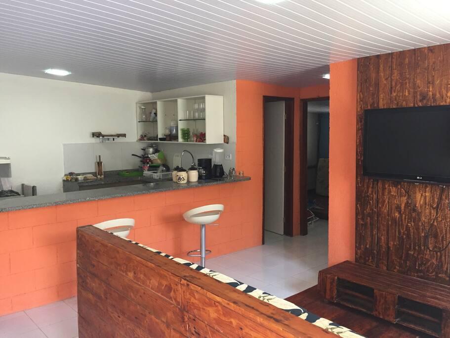 Casa principal com sala, cozinha americana, 2 quartos (1 suíte) e banheiro social.