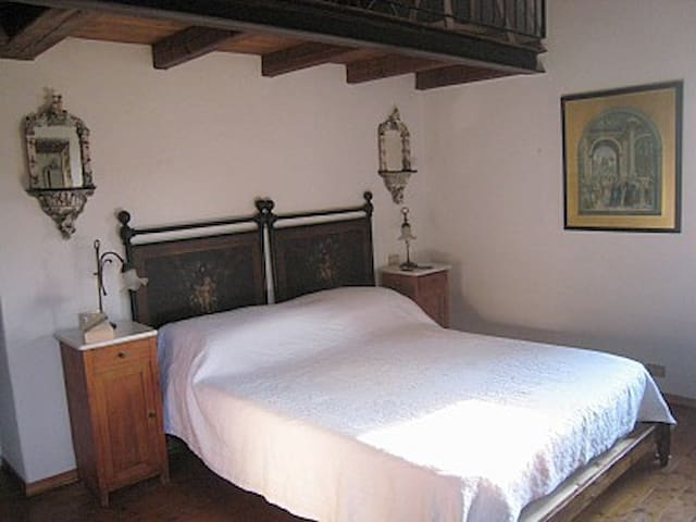 The master bedroom with 19th century painted bedheads