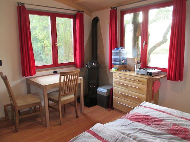 der Wohnbereich mit Küche, Holzofen und Tisch