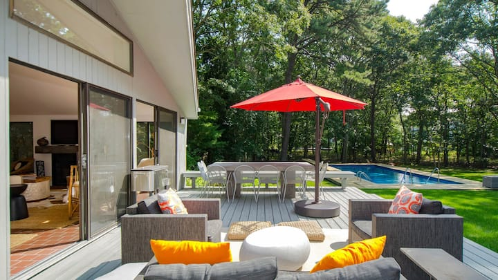 Impeccable Indoor/Outdoor Living on a Half-Acre in East Hampton w/ Wraparound Deck, Heated Pool