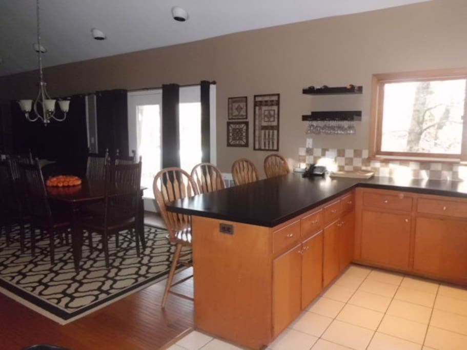 Large fully stocked kitchen with counter seating for 4 and open floor plan to dining and living room